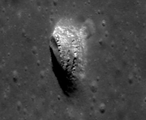 """I Mare Ingenii (""""Finurlighetens hav"""", fritt översatt) på månens bortre sida finns denna grop, ca 160 m i diameter, som Crawford pekar ut som en lämplig plats att leta efter supernovaspår på månen. De olika ljusa skikten som syns i gropen tillkom vid olika tider och kan bära spår av åtskilliga äldre supernovor i Vintergatan. Fotografiet togs av månsonden Lunar Reconnaisscance Orbiter. Bild: NASA/GSFC/ASU"""